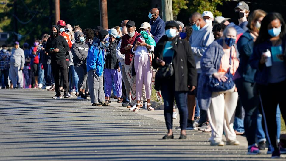 Early voters line up to cast their ballots at the South Regional Library polling location in Durham, N.C., Thursday, Oct. 15, 2020.