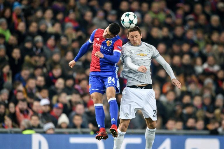 Basel's midfielder Mohamed Elyounoussi (L) and Manchester United's midfielder Nemanja Matic head the ball during the UEFA Champions League Group A football match November 22, 2017