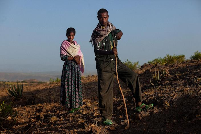 <p>Birara Dessie (25) and Haimanot Abera (14) married in June 2016, pose in a path in Gindero, Amhara, Ethiopia, in October 2016. When asked about her age, she says nothing and her husband answers for her. She is now out of school, helps her new family in the fields and takes care of the house work. The neighbour, part of the community council, that introduced the couple says she must be around 11 or 12. (Photo: José Colón/MeMo) </p>
