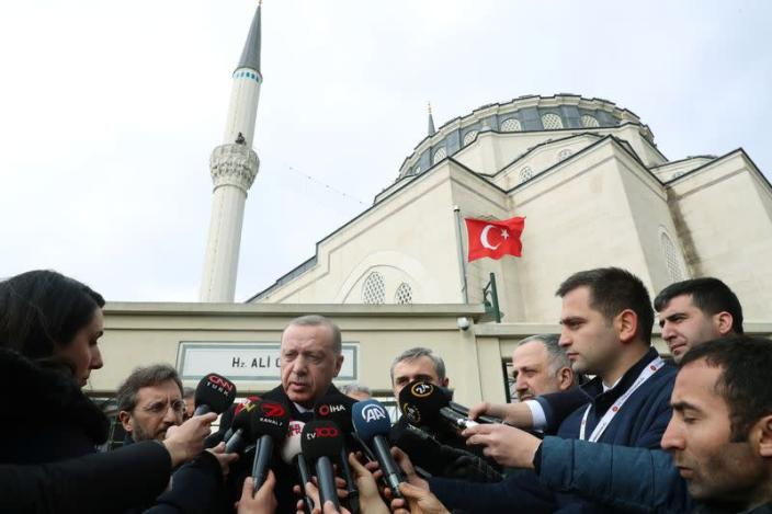 Turkish President Erdogan talks to journalists in front of a mosque as he leaves friday prayers in Istanbul