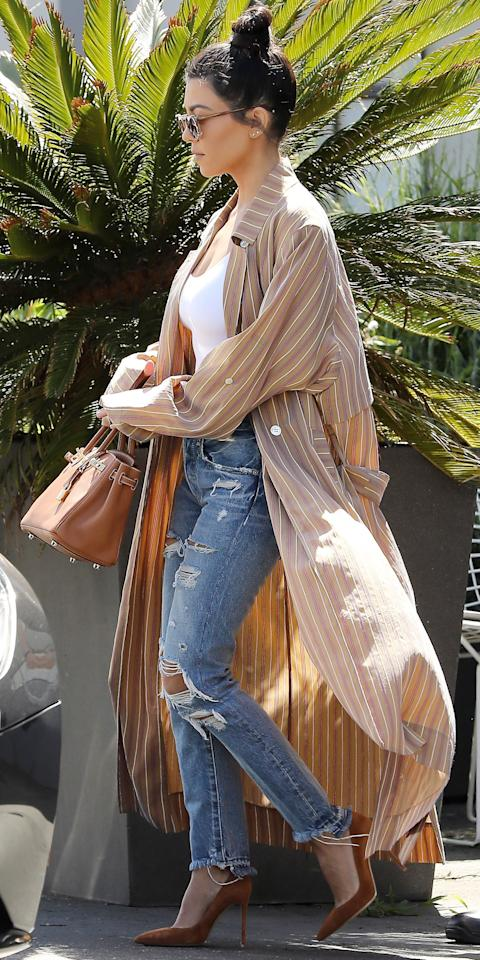 <p>The mother of three showed off her hip style in a floor-length striped robe top and distressed jeans while running errands in Los Angeles. She accessorized with rust-colored suede pumps, a matching leather bag, sunnies, and a chic topknot.</p>
