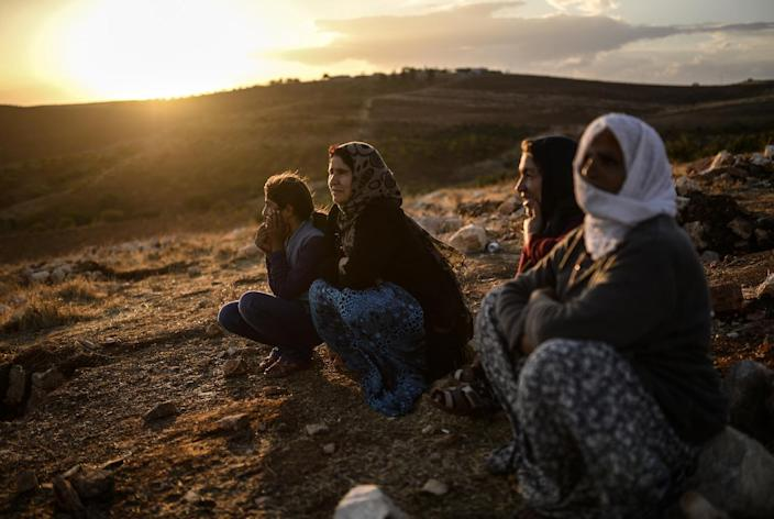 Syrian Kurds sit on a hill looking down on clashes between jihadists of the Islamic State (IS) and Kurdish fighters, close to the Turkish-Syrian border in Sanliurfa province, on September 28, 2014 (AFP Photo/Bulent Kilic)