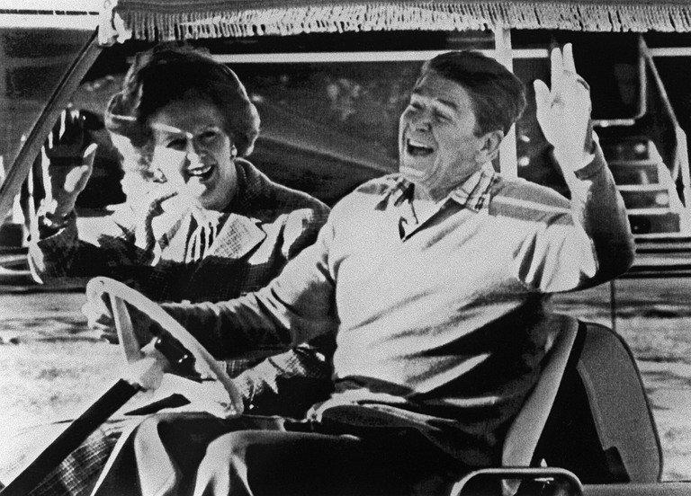"""Ronald Reagan (right) and Margaret Thatcher wave after arriving in Camp David in the United States on 22 December 1984. Former prime minister Margaret Thatcher, the controversial """"Iron Lady"""" who shaped a generation of British politics and was a pivotal figure in the Cold War, died following a stroke on Monday. She was 87"""