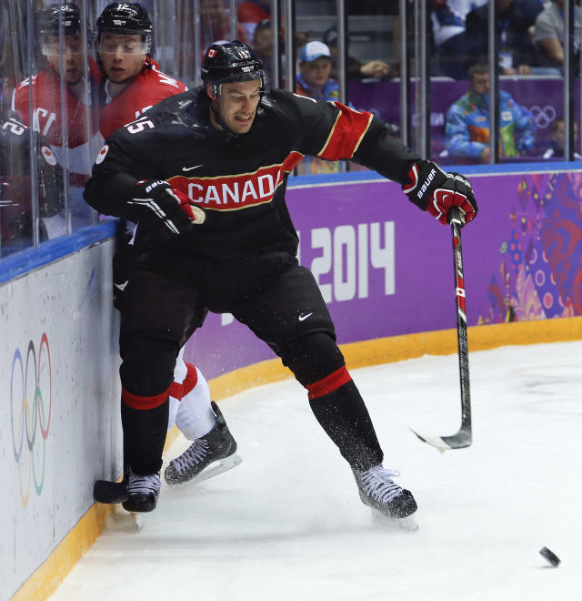 Canada forward Ryan Getzlaf seals off Austria forward Michael Raffl from the puck in the first period of a men's ice hockey game at the 2014 Winter Olympics, Friday, Feb. 14, 2014, in Sochi, Russia. (AP Photo/Mark Humphrey)