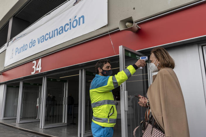 A worker from the Madrid Medical Emergency Service takes the temperature of a woman who is going to be vaccinated against COVID-19 at the Wanda Metropolitano stadium, Madrid, Spain, March 30, 2021. Spain is trying to stamp out a new wave of COVID-19 among its youth thanks to a robust vaccination program that is widely supported. Spain like the rest of the European Union got off to a slow start to compared to the United States and Britain when the first vaccines were released. But it has quickly made up ground once deliveries by drug makers started flowing. (AP Photo/Olmo Calvo)
