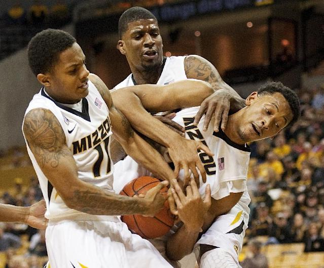 Missouri's Shane Rector, left, Tony Criswell, center, and Johnathan Williams III, right, fight each other for a rebound during the first half of an NCAA college basketball game against West Virginia Thursday, Dec. 5, 2013, in Columbia, Mo. (AP Photo/L.G. Patterson)