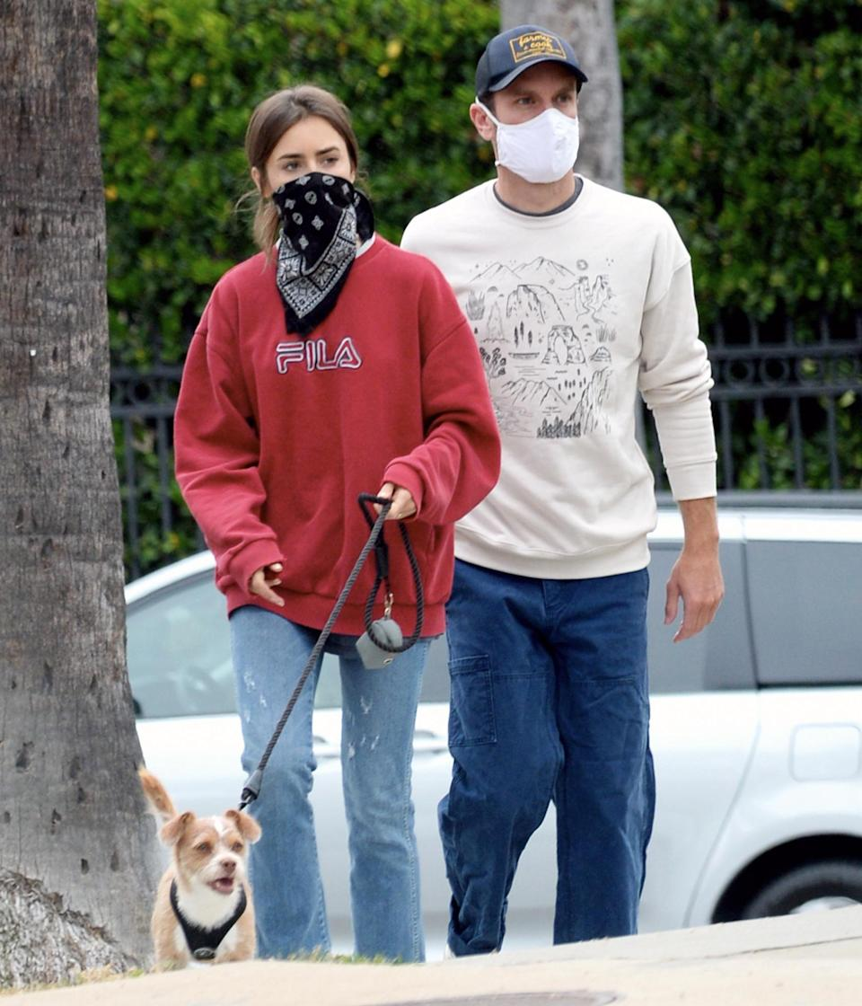 <p>Lily Collins and boyfriend Charlie McDowell take their dog for a walk in L.A. on Thursday.</p>