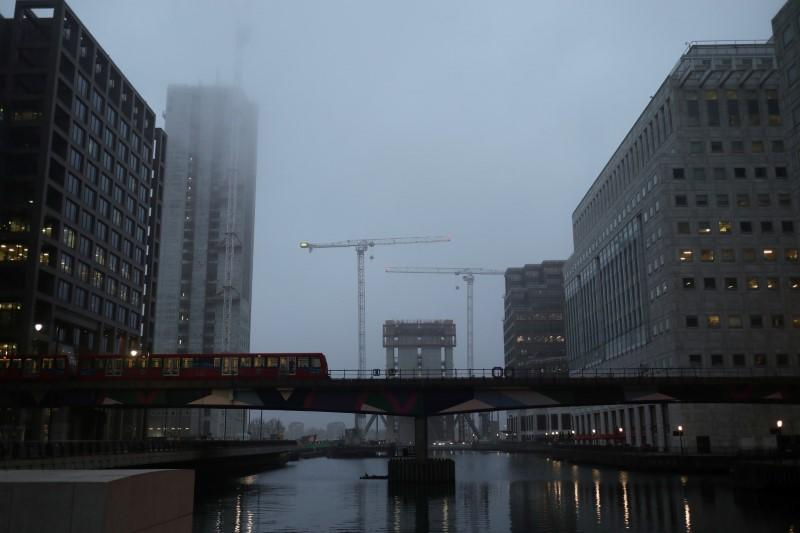 A DLR train crosses a bridge in front of construction work in early morning mist in London's Canary Wharf financial district in London