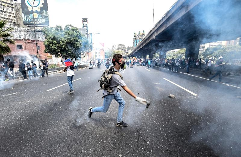 """Venezuelan opposition activists chanting """"No more dictatorship!"""" hurled stones at National Guard riot police who blocked them from marching on central Caracas (AFP Photo/JUAN BARRETO)"""