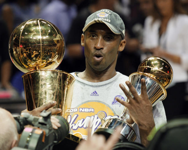 FILE - In this June 14, 2009 file photo Los Angeles Lakers' Kobe Bryant holds the Larry O'Brien championship trophy and finals MVP trophy after the Lakers defeated the Orlando Magic 99-86 in Game 5 of the NBA basketball finals in Orlando, Fla. Bryant, the 18-time NBA All-Star who won five championships and became one of the greatest basketball players of his generation during a 20-year career with the Los Angeles Lakers, died in a helicopter crash Sunday, Jan. 26, 2020. He was 41. (AP Photo/David J. Phillip)