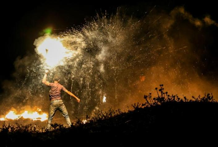 A Palestinian protester throws a burning projectile towards Israeli forces during a demonstration east of Gaza City
