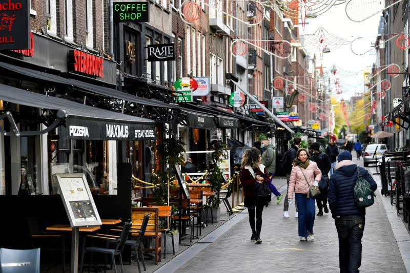 FILE PHOTO: People walk past restaurants and bars in Amsterdam.