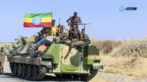 """This image made from undated video released by the state-owned Ethiopian News Agency on Monday, Nov. 16, 2020 shows Ethiopian military sitting on an armored personnel carrier next to a national flag, on a road in an area near the border of the Tigray and Amhara regions of Ethiopia. Ethiopia's prime minister Abiy Ahmed said in a social media post on Tuesday, Nov. 17, 2020 that """"the final and crucial"""" military operation will launch in the coming days against the government of the country's rebellious northern Tigray region. (Ethiopian News Agency via AP)"""