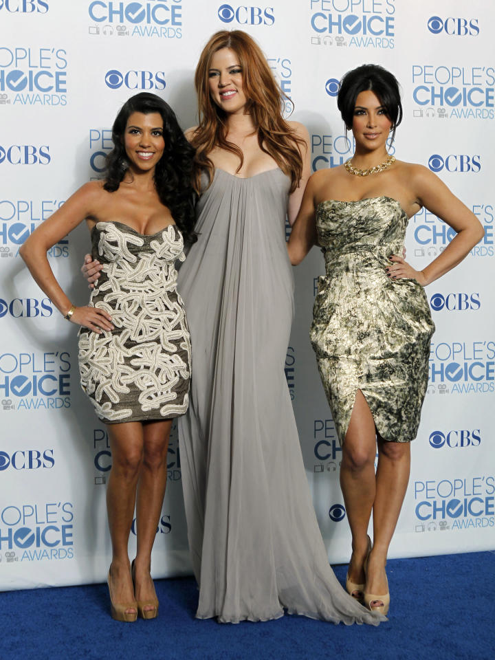 """FILE - In this Jan. 5, 2011 file photo, from left, Kourtney Kardashian, Khloe Kardashian, and Kim Kardashian pose for a photo backstage with the award for favorite TV guilty pleasure for """"Keeping Up with the Kardashians"""" at the People's Choice Awards in Los Angeles. A Central California judge has thrown out a lawsuit filed against the Kardashian sisters after they pulled their endorsement of a prepaid debit card that drew criticism for its high fees. (AP Photo/Matt Sayles, file)"""