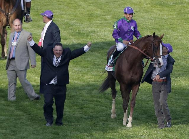 Assistant trainer Alan Sherman, left, after Victor Espinoza rode California Chrome to victory in the 140th running of the Kentucky Derby horse race at Churchill Downs Saturday, May 3, 2014, in Louisville, Ky. (AP Photo/Charlie Riedel)
