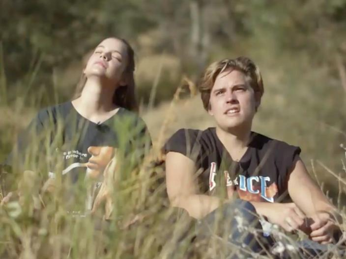 barbara palvin and dylan sprouse sitting in a sunny field by a lake