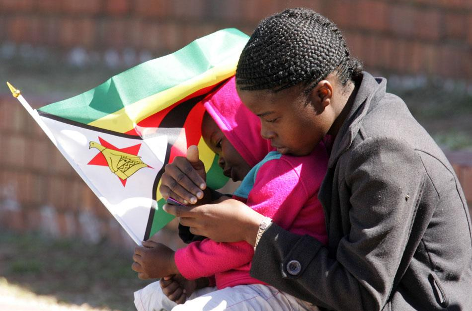 A woman, supporter of Zimbabwe, and a child hold a Zimbabwean flag  during the 4th match of the 5-match cricket ODI series between Zimbabwe and India at Queen's Sports Club in Harare on August 1, 2013. AFP PHOTO / Jekesai Njikizana        (Photo credit should read JEKESAI NJIKIZANA/AFP/Getty Images)