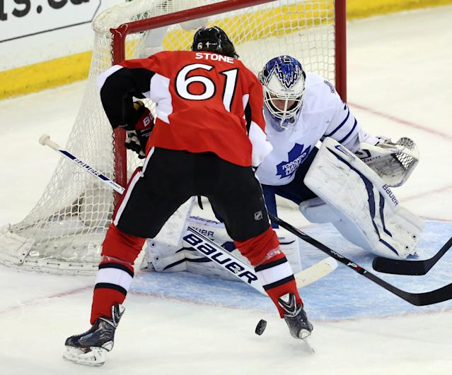 Ottawa Senators' Mark Stone (61) has the puck knocked away by Toronto Maple Leafs goaltender James Reimer during first-period NHL hockey game action in Ottawa, Ontario, Saturday, April 12, 2014. There was no goal scored on the play. (AP Photo/The Canadian Press, Fred Chartrand)