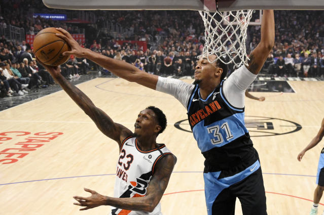 Los Angeles Clippers guard Lou Williams, left, has his shot blocked by Cleveland Cavaliers forward John Henson during the first half of an NBA basketball game Tuesday, Jan. 14, 2020, in Los Angeles. (AP Photo/Mark J. Terrill)