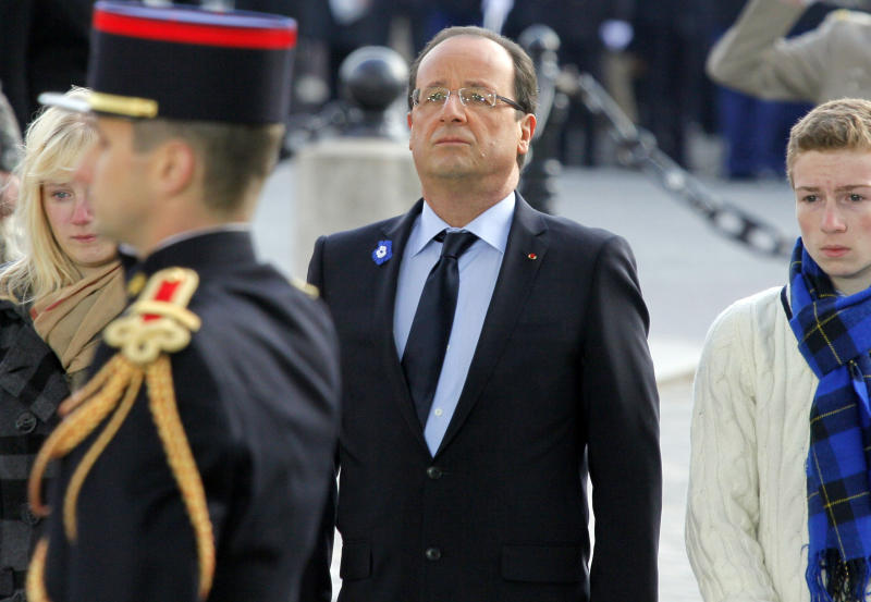French President Francois Hollande, centre, stands with the unidentified children of soldiers killed in Afghanistan, during the Armistice Day ceremony, in Paris, Sunday, Nov. 11, 2012. President Francois Hollande reviewed troops around Paris' iconic Arc de Triomphe and laid a wreath on the tomb of the unknown solider beneath the arch to commemorate France's war dead. Nov. 11 marks the signing of the truce that ended the fighting in World War I and had previously been reserved for remembering the more than 1 million French soldiers killed in that war. Hollande was accompanied Sunday by the children of soldiers who were killed in Afghanistan — a nod to the country's decision last year to commemorate all of its war dead on Armistice Day.  (AP Photo/Michel Spingler, Pool)