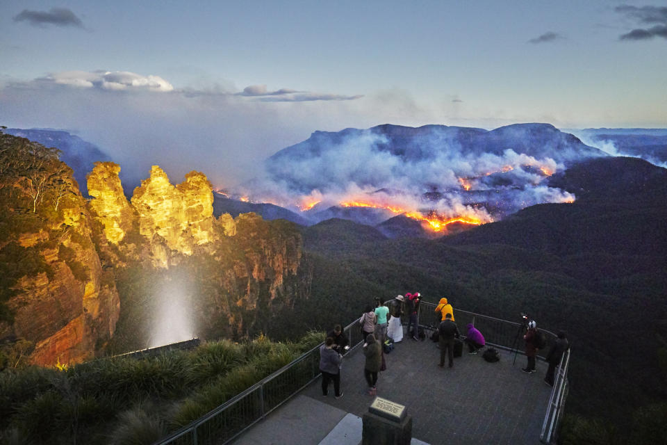 Tourists watch the bush-fire from the safety of the Echo Point Lookout. The World Heritage listed Blue Mountains National Park is one of Australia's most popular tourist destinations. It includes the famous Three Sisters rock formation.
