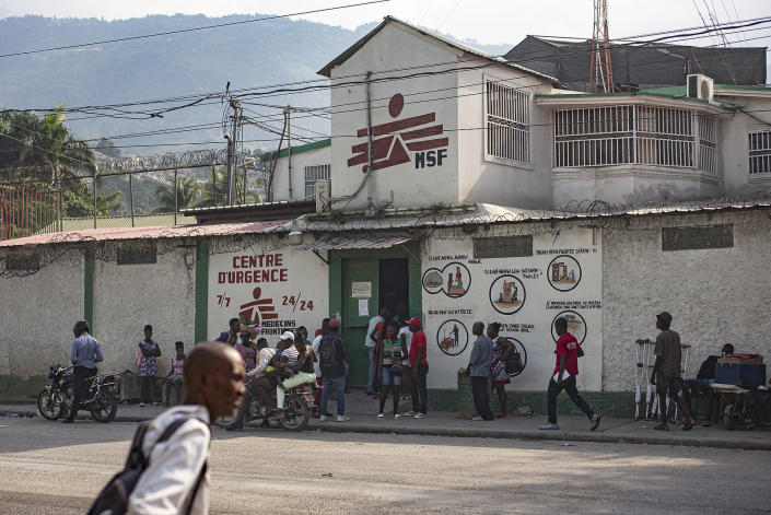 This photo provided by Doctors Without Borders shows locals standing outside its emergency clinic in the Martissant neighborhood of Port-au-Prince, Haiti, Sunday, Dec. 2, 2020. Officials said Monday, August 2, 2021, that Doctors Without Borders has closed the Martissant emergency clinic in Haiti's capital amid gang violence that has left more than 19,000 people homeless. (Guillaume Binet/Doctors Without Borders via AP)