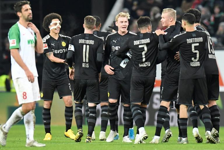 Dortmund's Norwegian forward Erling Braut Haaland (3rdR) is congratulated by teammates after scoring a hat-trick on his debut in the 5-3 win at Augsburg on Saturday. (AFP Photo/THOMAS KIENZLE)