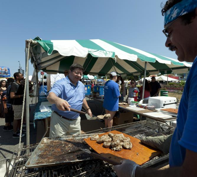 Chef Dirk Fucik, right, gathers Asian carp patties from the barbecue to serve to visitors at the Taste of Chicago Festival on Wednesday, July 11, 2012 in Chicago. State officials ave been trying to change the perception of the pest fish, calling it a nutritious food that could become a consumer item. (AP Photo/Sitthixay Ditthavong)