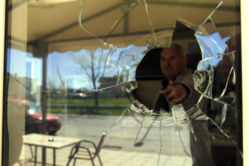 Kostas Tassios, a coffee shop owner, points at a bullet hole in the window his coffee shop near the city of Trikala, central Greece, on Saturday, March 23, 2013. At least 11 inmates escaped from a Greek prison after gunmen brazenly attacked the site with grenades and automatic weapons, kicking off a nightlong standoff between police and prisoners. Two guards were injured, one of them seriously. The attack was the latest dramatic incident at Greek prisons, which are suffering from serious overcrowding and staff shortages as the country struggles through financial crisis and a recession that started in late 2008.(AP Photo/Nikolas Giakoumidis)