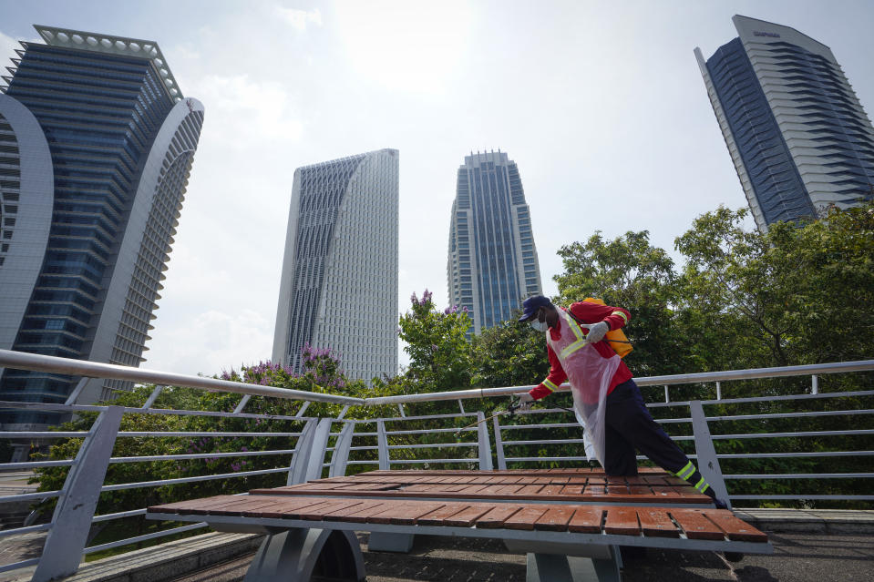 City hall workers spray disinfectant in Putrajaya, Malaysia, on Monday, Oct. 19, 2020. Malaysia restrict movements in its biggest city Kuala Lumpur, neighboring Selangor state and the administrative capital of Putrajaya from Wednesday in an attempt to curb a sharp rise in coronavirus cases. (AP Photo/Vincent Thian)