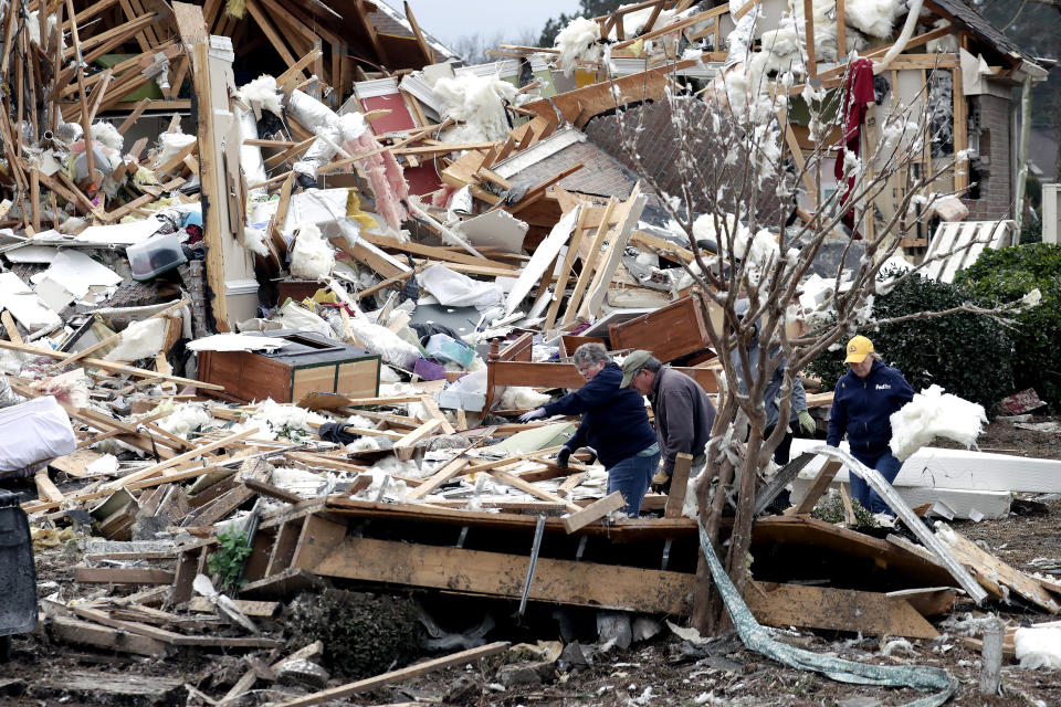 People sift through the rubble of homes at the Ocean Ridge Plantation in Brunswick County, N.C., Wednesday, Feb. 17, 2021, after a tornado hit the area Monday night. (AP Photo/Chris Seward)