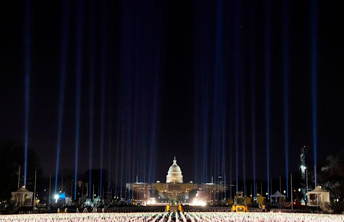 "Lights were beamed into the sky surrounding the ""Field of Flags"" as inauguration week kicked off Monday. (Photo: TIMOTHY A. CLARY via Getty Images)"