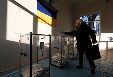 A woman casts a ballot during a parliamentary election at a school gym in the village of Semyonovka near Slaviansk, eastern Ukraine, October 26, 2014. REUTERS/Vasily Fedosenko