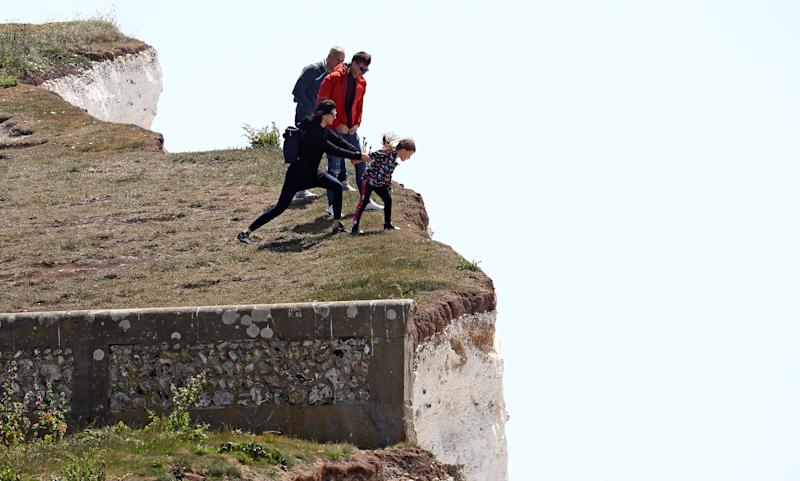 A young girl is held back as she peers over the edge of cliffs at Birling Gap.