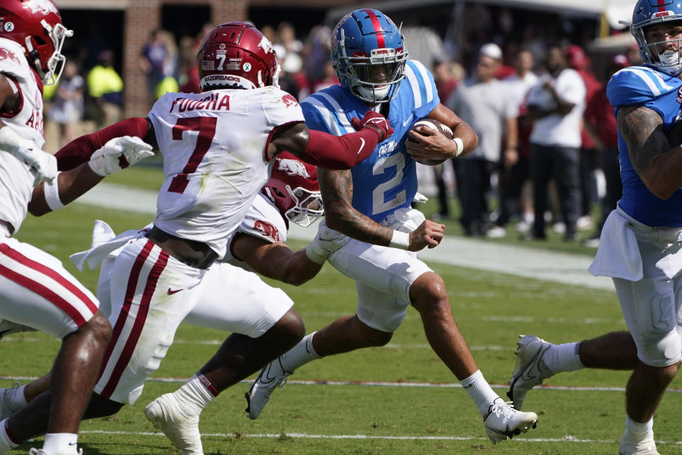 Mississippi quarterback Matt Corral (2) runs for a first down while being pursued by Arkansas defensive back Joe Foucha (7) during the first half of an NCAA college football game against Arkansas, Saturday, Oct. 9, 2021, in Oxford, Miss. (AP Photo/Rogelio V. Solis)