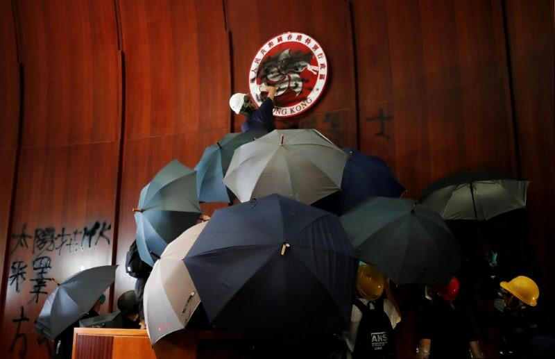 FILE PHOTO: A person sprays paint over Hong Kong's coats of arms inside a chamber after protesters broke into the Legislative Council building during the anniversary of Hong Kong's handover to China in Hong Kong