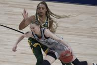UConn's Paige Bueckers drives past Baylor's DiJonai Carrington during the second half of an NCAA college basketball game in the Elite Eight round of the Women's NCAA tournament Monday, March 29, 2021, at the Alamodome in San Antonio. (AP Photo/Morry Gash)