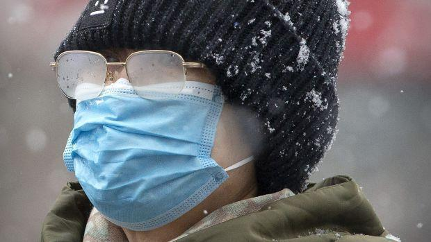 A woman's eyeglasses are fogged up as she wears a face mask during a snowfall in Beijing, Sunday, Feb. 2, 2020.