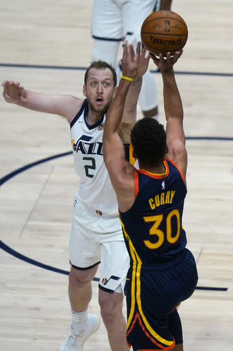 Golden State Warriors guard Stephen Curry (30) shoots as Utah Jazz forward Joe Ingles (2) defends during the first half of an NBA basketball game Saturday, Jan. 23, 2021, in Salt Lake City. (AP Photo/Rick Bowmer)