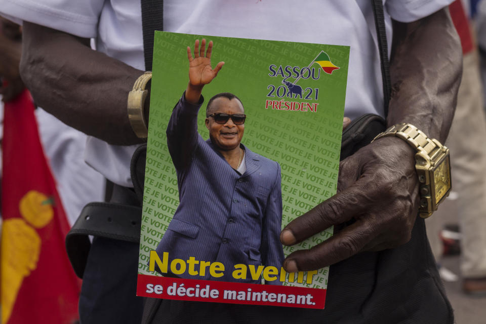 A supporter of President Denis Sassou N'Guesso holds his photo during the last rally of the presidential campaign in Brazzaville, Congo, Friday March 19, 2021. After 36 years in power, Republic of Congo's President Denis Sassou N'Guesso appears poised to extend his tenure as one of Africa's longest-serving leaders in the elections to be held Sunday amid opposition complaints of interference with their campaigns. (AP Photo/Zed Lebon)