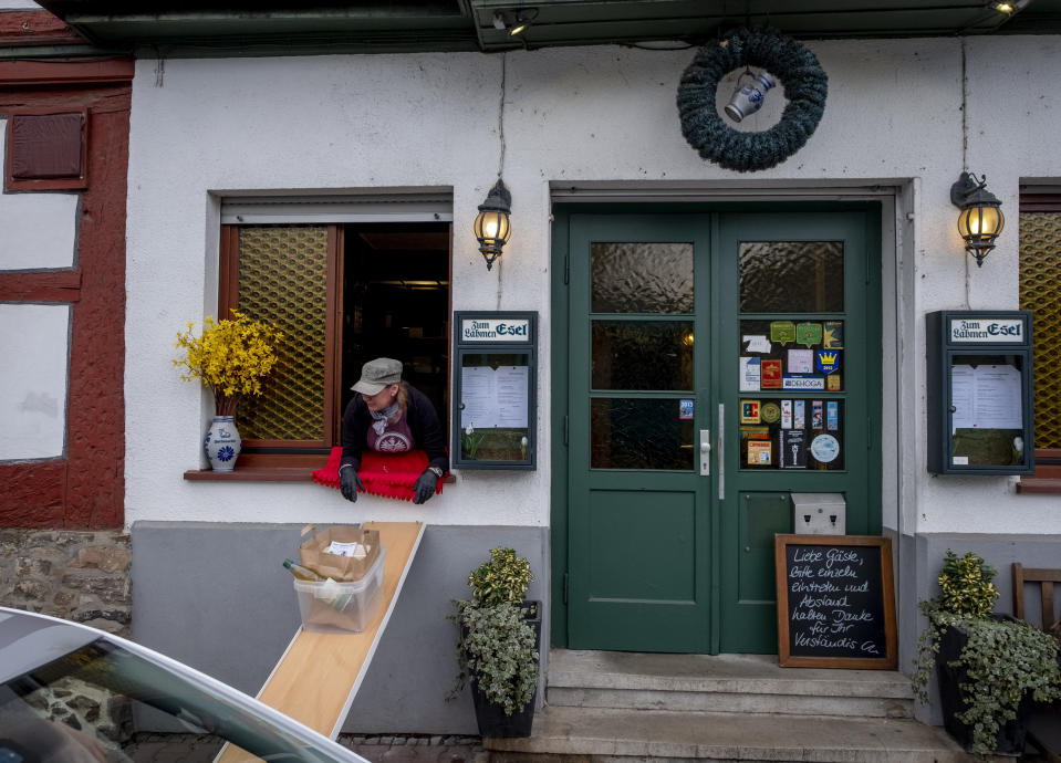 Food slides down to car from a window of the apple cider restaurant 'Zum Lahmen Esel' in Frankfurt, Germany, Friday, April 3, 2020. Due to the coronavirus outbreak the restaurant which has been in operation since 1807 offers cider and food to go in a self-made drive through set up. (AP Photo/Michael Probst)