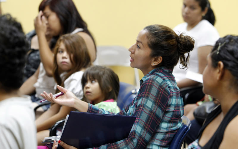 Participants and their children, most born in the United States, attend an orientation seminar for illegal immigrants, to determine if they qualify for temporary work permits, at the Coalition for Humane Immigrant Rights of Los Angeles (CHIRLA), in Los Angeles, Thursday, Sept. 20, 2012. Schools and consulates have been flooded with requests for documents since President Barack Obama's administration said many young illegal immigrants may be eligible for two-year renewable work permits. The new policy has left schools and consulates scrambling for quick fixes ranging from new online forms, reassigned workers and extended hours.  (AP Photo/Reed Saxon)