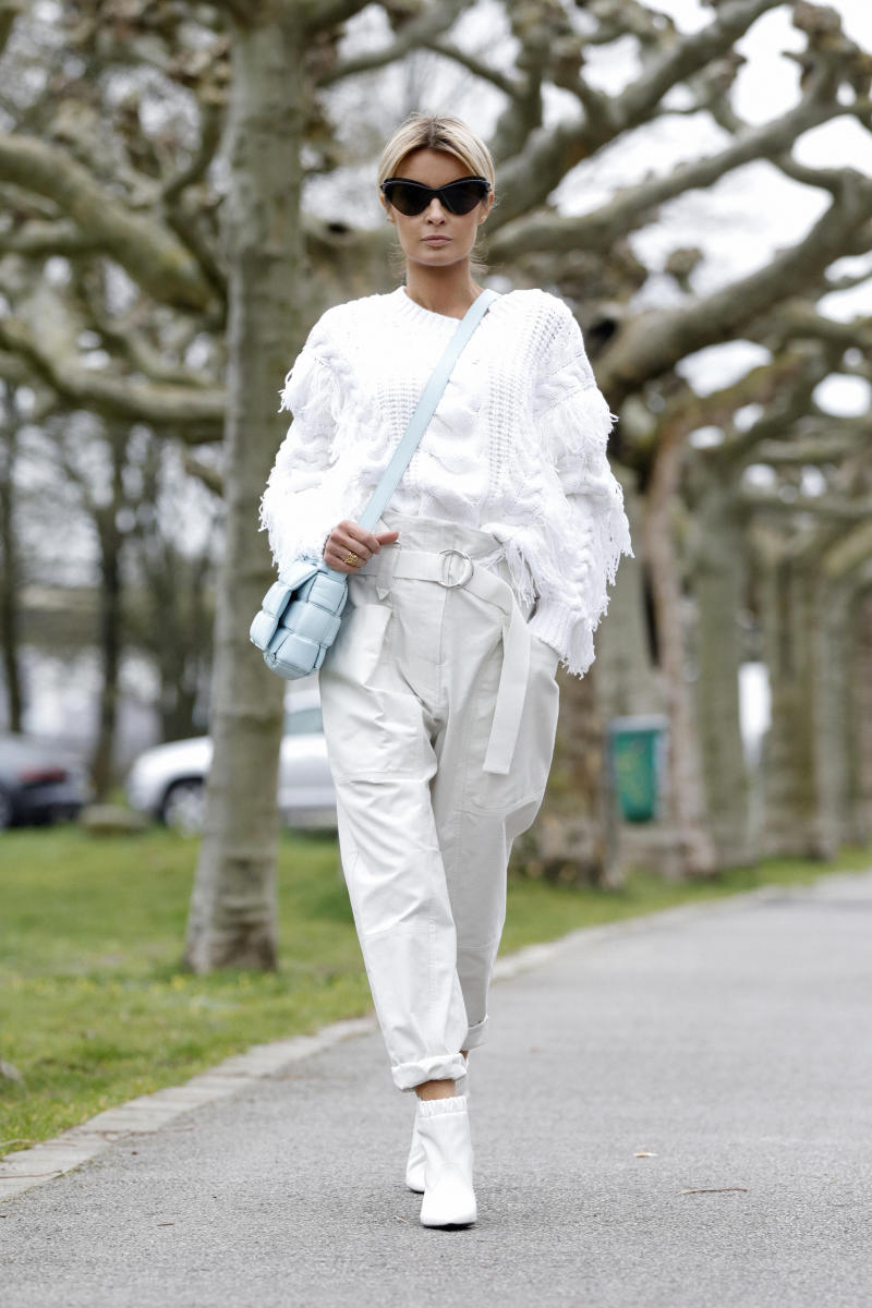 DUSSELDORF, GERMANY - MARCH 20: Influencer Gitta Banko, wearing a white fringed sweater and paperbag pants by Iro, white booties by Celine, topaz padded casette bag by Bottega Veneta and sunglasses by Mykita x Maison Margiela during a street style shooting on March 20, 2020 in Dusseldorf, Germany. (Photo by Isa Foltin/Getty Images)