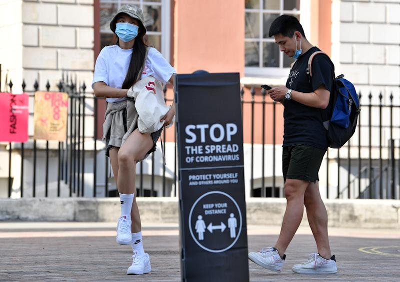 "People wearing a face mask or covering due to the COVID-19 pandemic, stand near a sign reading ""Stop the spread of Coronavirus"" in Covent Garden, London on September 22, 2020. - The British government announced fresh steps Tuesday to try and stop a coronavirus surge in England, as the World Health Organization warned that new cases worldwide soared to almost two million last week in a grim new record. The measure included early closing time for pubs and restaurants, a resumption of advice for people to work from home, coupled with new penalties for breaking the rules. (Photo by Ben STANSALL / AFP) (Photo by BEN STANSALL/AFP via Getty Images)"