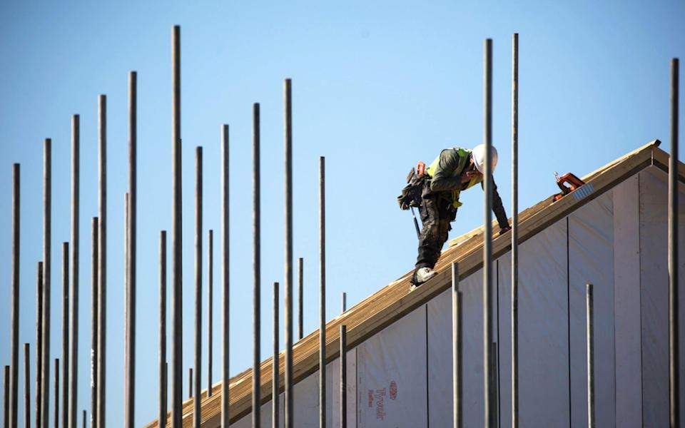 An employee works on the roof of a residential property under construction