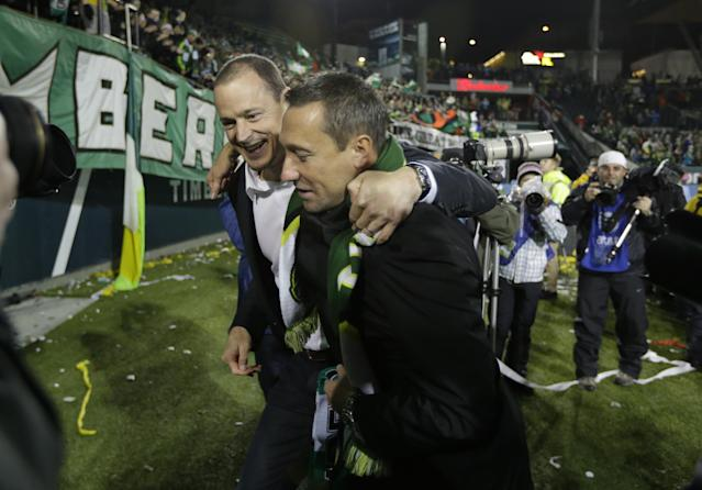 Portland Timbers owner Merritt Paulson, left, walks off the pitch with Portland Timbers head coach Caleb Porter, right, after the Timbers beat the Seattle Sounders 3-2 in the second game of the Western Conference semifinals in the MLS Cup soccer playoffs, Thursday, Nov. 7, 2013, in Portland, Ore. The win gave the Timbers a 5-3 aggregate score in the two-match series and the Timbers will to the Western Conference semifinals against Real Salt Lake. (AP Photo/Ted S. Warren)