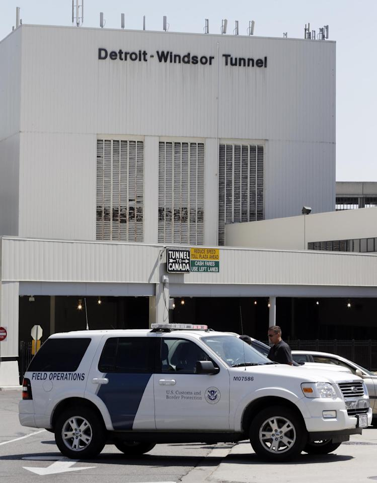 Vehicles block the entrance as authorities investigate a bomb threat at the Detroit Windsor Tunnel Thursday, July 12, 2012. The tunnel was closed to traffic after the threat was called in on the Canadian side, tunnel chief executive Neal Belitsky told The Associated Press. The call was made some time after 12:30 p.m. to the duty free shop on a plaza on the tunnel's Windsor side, tunnel executive vice president Carolyn Brown said. The underwater tunnel stretches about a mile beneath the Detroit River, which is one of North America's busiest trade crossings. (AP Photo/Paul Sancya)