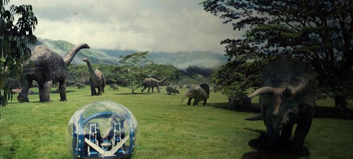 A gyrosphere rolling across a green space with dinosaurs