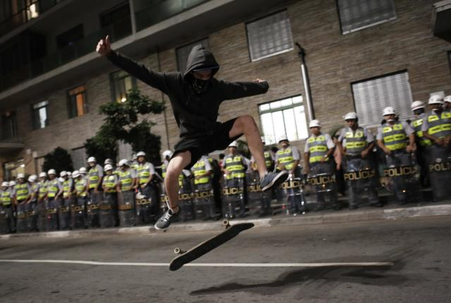 A demonstrator whose face is obscured by a handkerchief performs with his skateboard in front of military policemen during a protest against the 2014 World Cup in Sao Paulo March 27, 2014. REUTERS/Nacho Doce (BRAZIL - Tags: SPORT SOCCER WORLD CUP CIVIL UNREST TPX IMAGES OF THE DAY)
