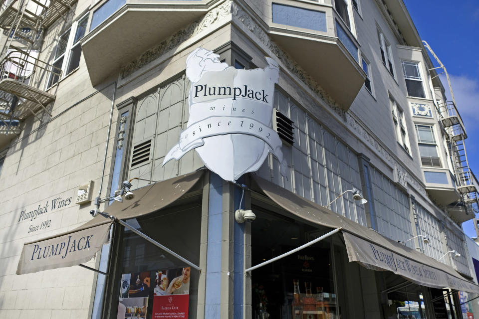 FILE - This Oct. 22, 2018, file photo shows the PlumpJack Wine & Spirits store in San Francisco. Law enforcement officials are investigating escalating threats of death and violence against California Gov. Gavin Newsom, his family and the the wineries, shops and other businesses he founded. False rumors spread online that Newsom has given coronavirus aid money to his own businesses. In fact, PlumpJack Group received about $2.8 million in loans through the Paycheck Protection Program administered by the federal government, not California. Newsom placed all of his businesses in a blind trust when he took office to reduce potential conflicts of interest. The trust legally bars him from being involved in the businesses' day-to-day operations or participating in buy-and-sell decisions. (AP Photo/Eric Risberg, File)